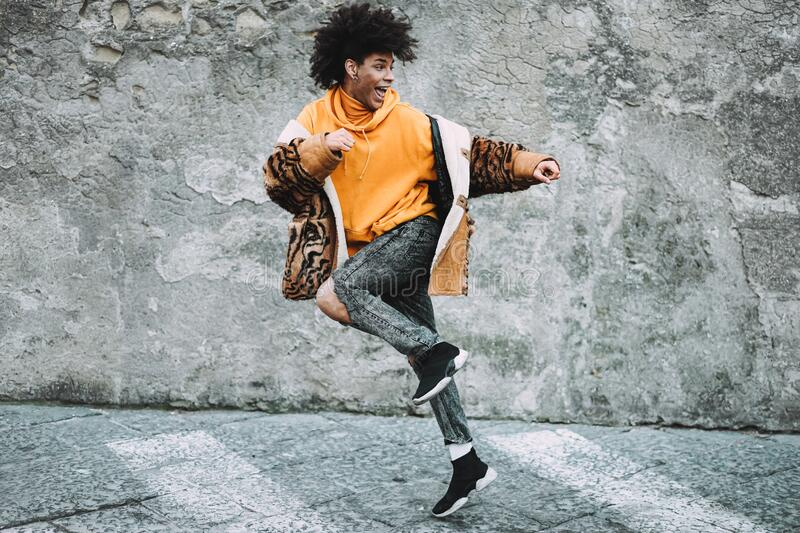Stylish millennial guy dancing around city street outdoor - Young man having fun outside wearing trendy clothes - Z generation and. Fashion concept - Focus on stock photos