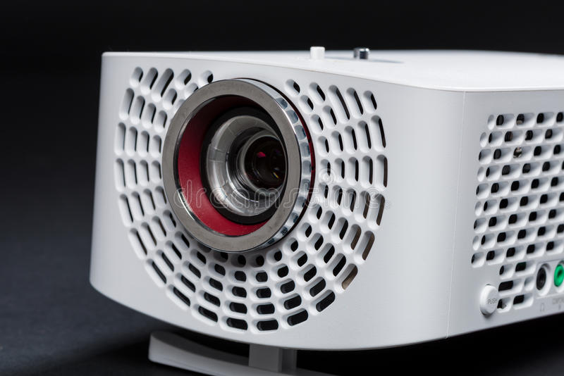 Stylish mini home cinema LED projector, lightweight tech gadget royalty free stock images