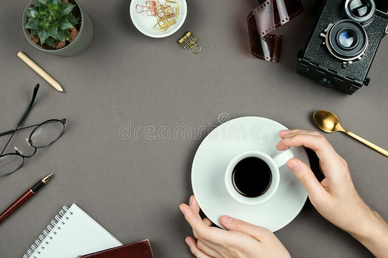 Stylish minimalist mockup with notebook, planner, glasses, vintage camera and woman`s hands holding cup of coffee royalty free stock image