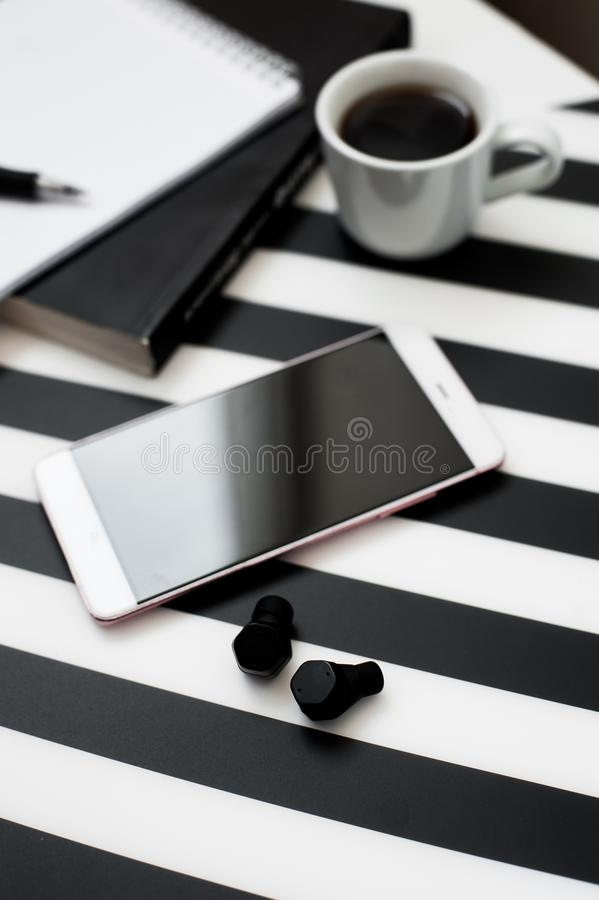 Workspace with smartphone mock up, book, notebook, pencil, cup of coffee, wireless earphones striped black and white background. royalty free stock images