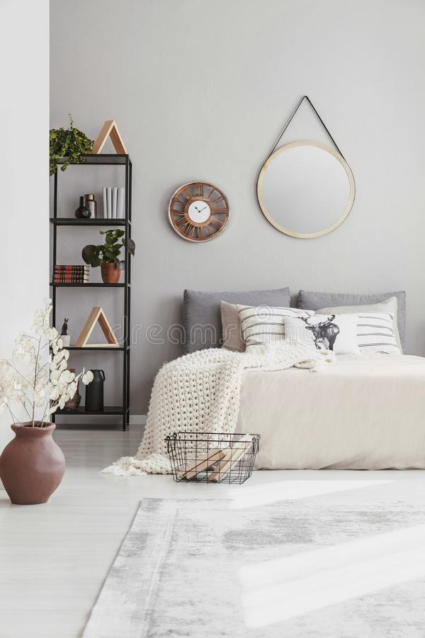 Stylish mirror and clock on the wall of warm ethno bedroom with comfortable king size bed. With lot of pillows and blanket stock photos