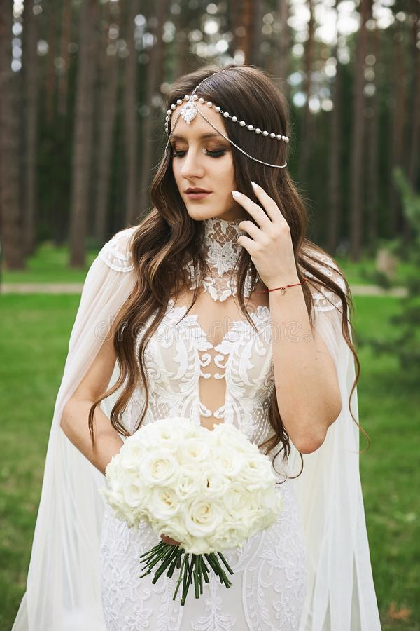 Stylish model girl with jewelry in her wedding hairstyle and bright makeup wearing in lace wedding dress keeping a stock image