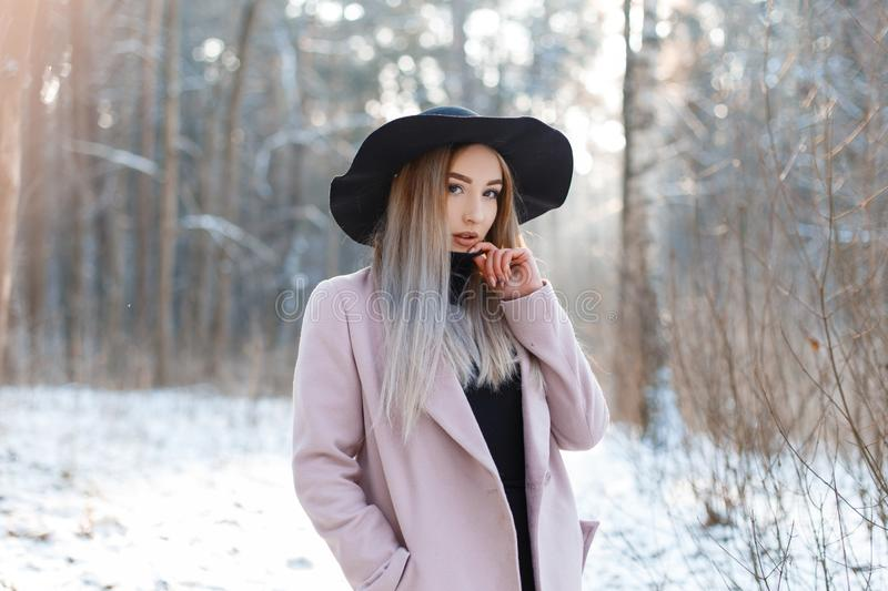 Stylish modern beautiful young woman in a knitted vintage dress in a stylish black hat in a pink elegant coat posing in the woods. On a background of snowy stock image