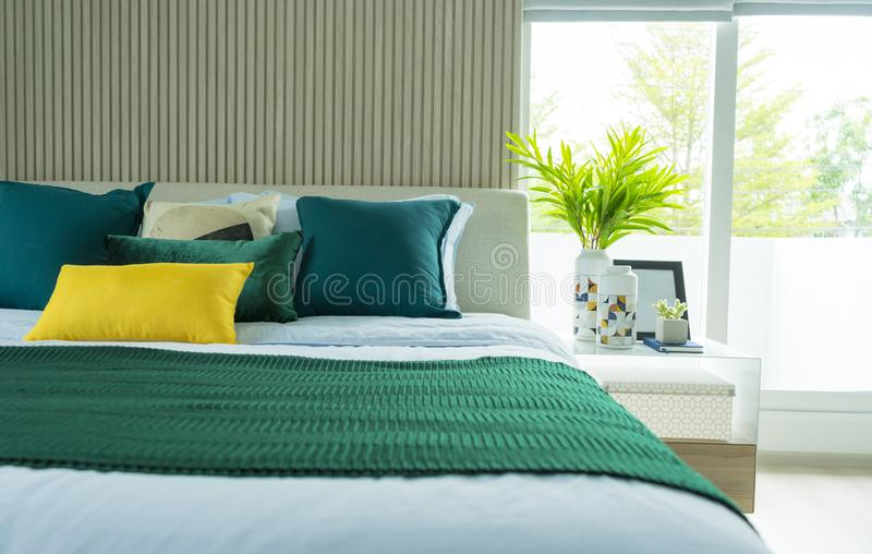 Stylish modern bedroom interior. green, yellow and blue pillow on comfortable bed. Luxury and stylish of modern bedroom interior. green, yellow and blue pillow stock photo