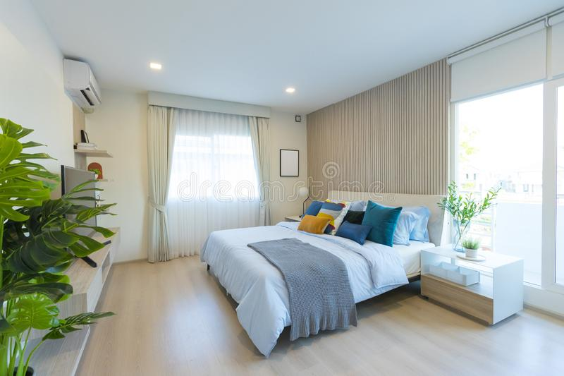 Stylish modern bedroom interior. green, yellow and blue pillow on comfortable bed. Luxury and stylish of modern bedroom interior. green, yellow and blue pillow royalty free stock images