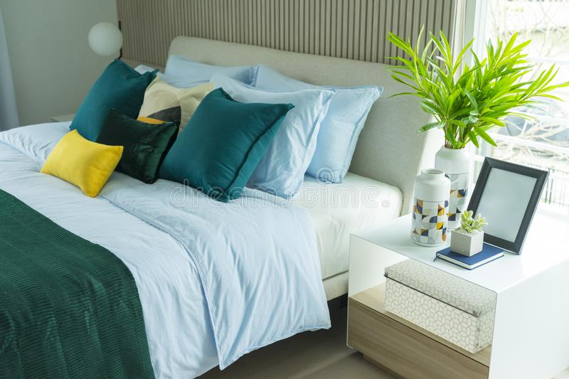 Stylish modern bedroom interior. green, yellow and blue pillow on comfortable bed. Luxury and stylish of modern bedroom interior. green, yellow and blue pillow stock images