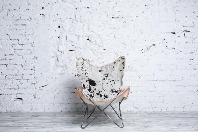Stylish modern chair with animal print in loft interior royalty free stock photography