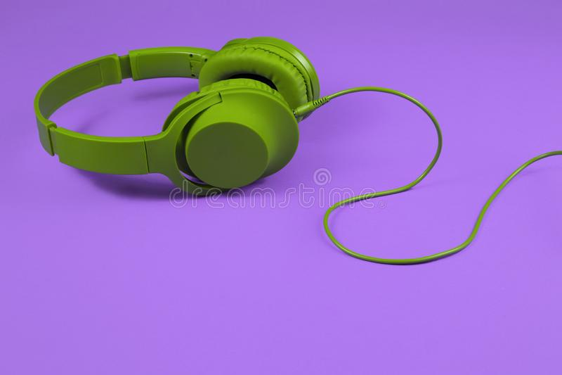 Stylish modern green cyan headphones isolated over purple background. Stylish modern green cyan headphones isolated over purple background royalty free stock photos