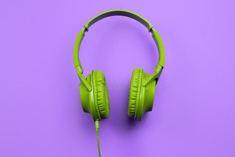Stylish modern green cyan headphones isolated over purple background. Stylish modern green cyan headphones isolated over purple background royalty free stock images