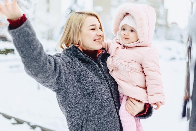 Stylish mom with baby walk at street on winter. Stylish young mom with baby walk at street on winter stock photography