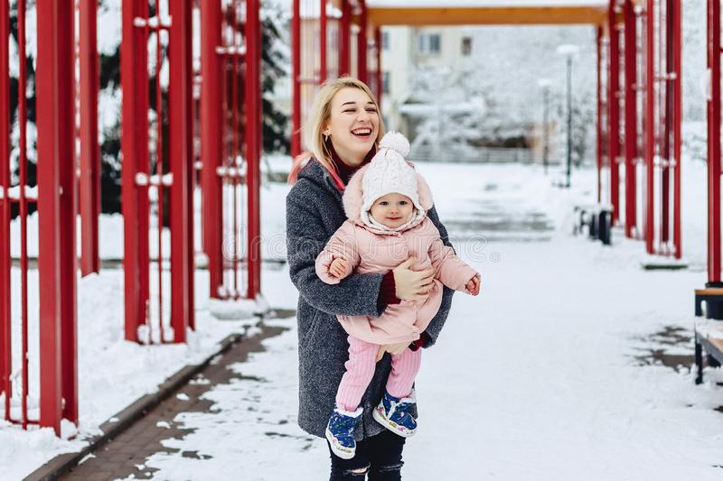 Stylish mom with baby walk at street on winter. Stylish young mom with baby walk at street on winter royalty free stock image