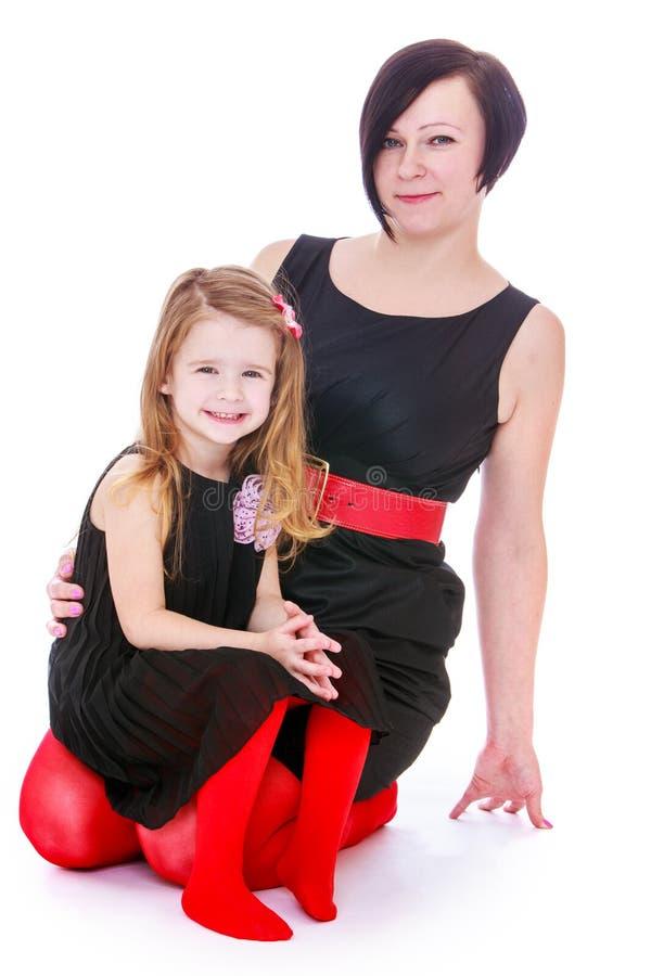 Stylish mother and daughter, studio shooting stock image