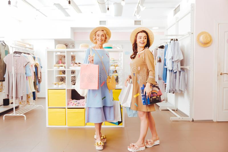 Stylish mother leaving showroom with purchases along with daughter royalty free stock images