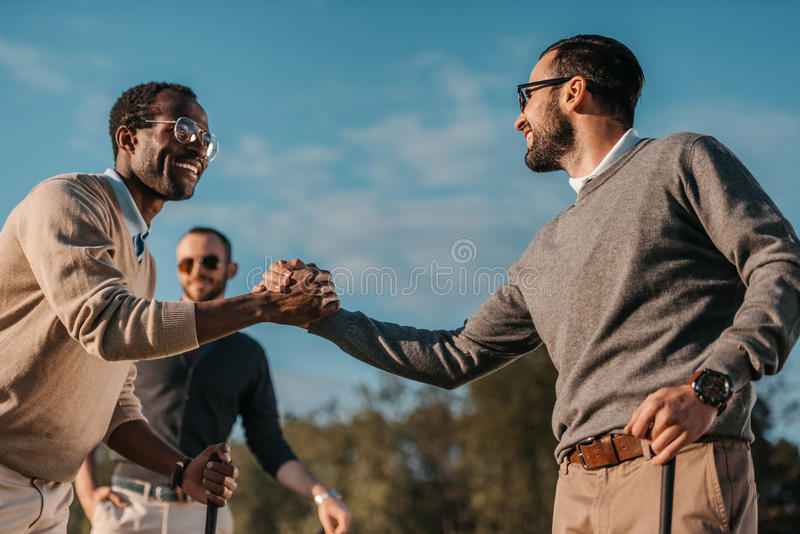 Stylish multicultural friends shaking hands while playing golf on golf course royalty free stock image