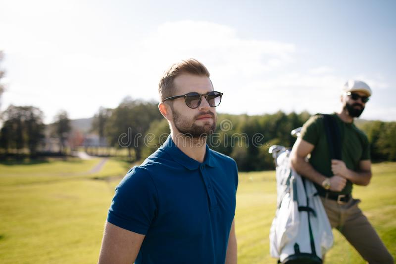Golf player walking and carrying bag on course during summer gam stock photo