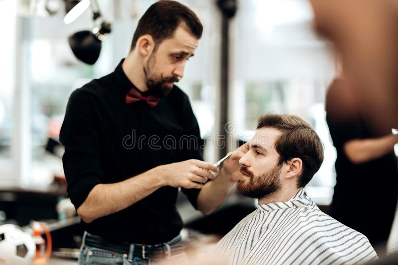 Stylish mustachioed barber dressed in a black shirt with a red bow tie scissors the hair of a young man in a barbershop stock photo