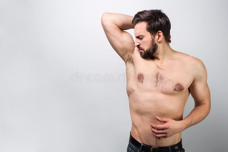 Stylish and almost naked guy is standing near big wall and smelling his armpit. He wants to make sure he smells good but stock images