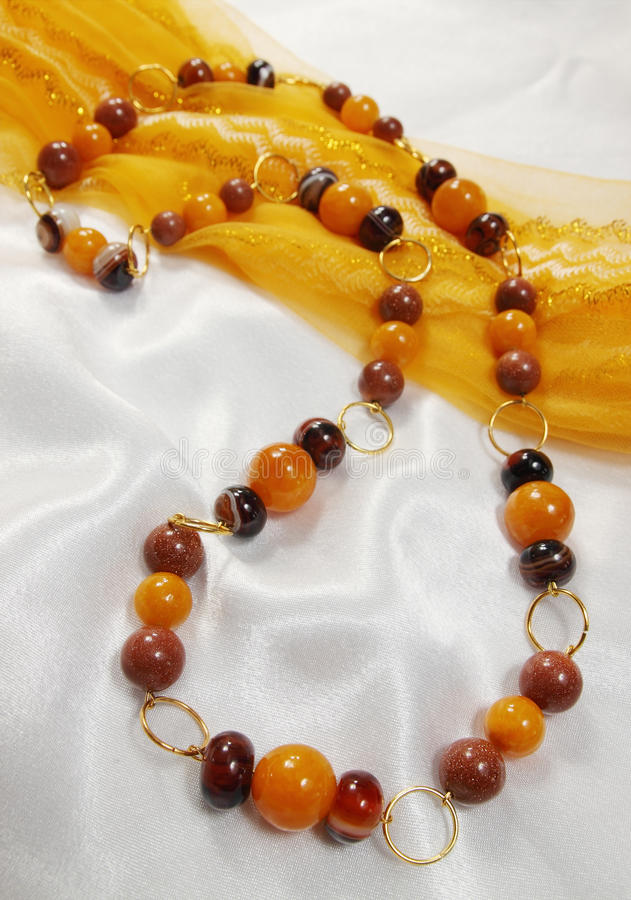 Stylish necklace. Of semiprecious stones in yellow and brown colors royalty free stock photo