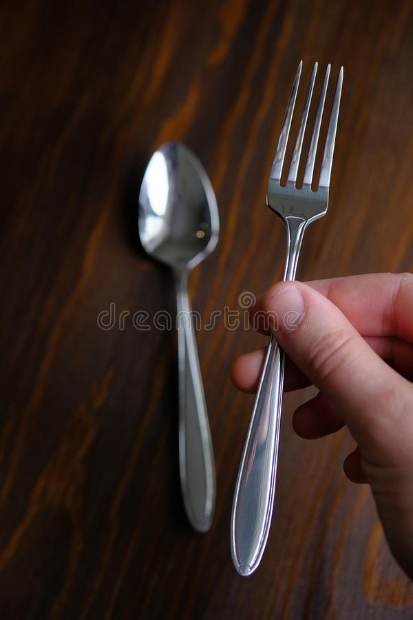 Stylish new fork in the hand of a man, lying next to a stainless steel spoon on the background of a wooden table, close-up. Blurred background. The concept of royalty free stock photo