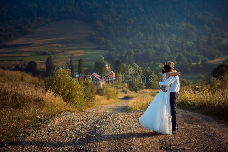 Stylish newlywed couple is hugging on the road at the background of the beautiful mountains during the sunset. royalty free stock photo