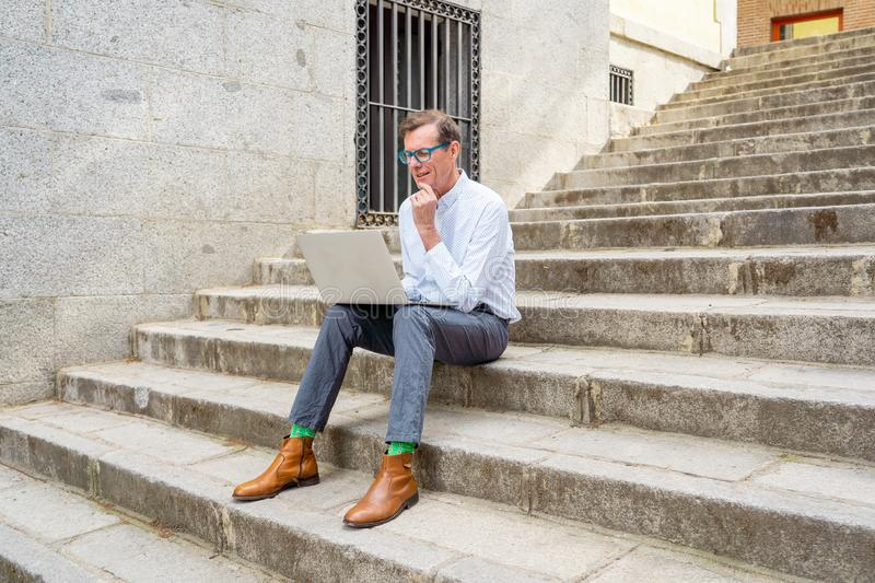 Stylish old man working on laptop surfing the internet sitting on stairs outdoors city in digital nomad Senior using modern. Technology Staying connected and royalty free stock photography