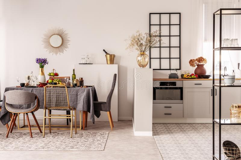Stylish open plan kitchen and dining room interior with white cupboard and long table with grey tablecloth and food.  stock photos