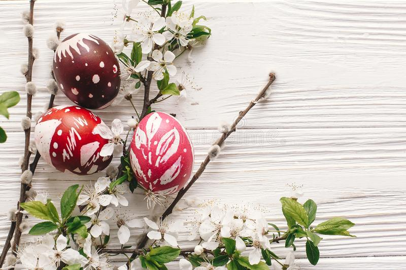 stylish painted easter eggs on rustic wooden background with spring flowers and willow branches. happy easter greeting card flat royalty free stock photo