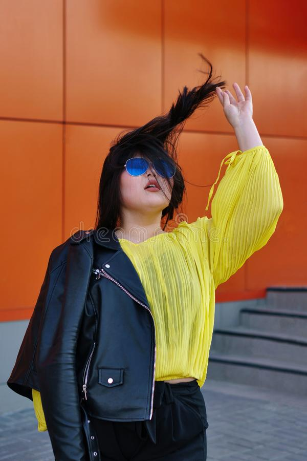 Stylish Pan-Asian girl posing outdoor. Stylish pan-Asian plus size girl in a leather jacket and sunglasses. She plays with her long black hair in the wind stock image