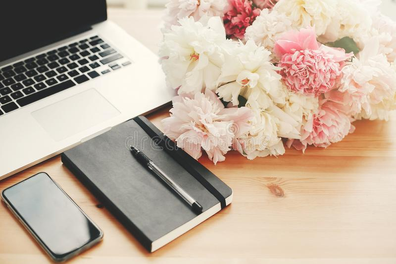 Stylish phone with empty screen, laptop, notebook, pen, pink and white peonies on wooden table with space for text. Freelance royalty free stock image