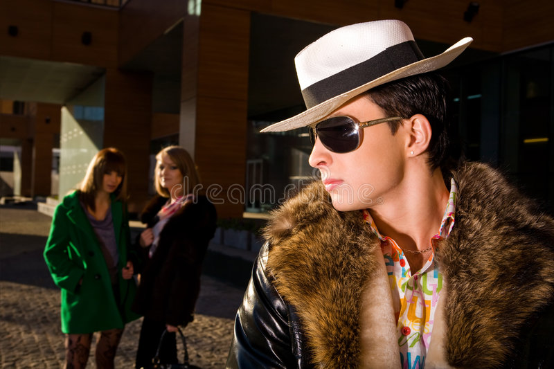 Stylish pimp and two young women stock photo