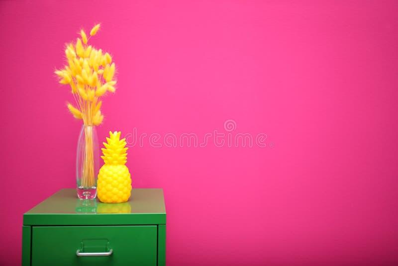 Stylish pineapple candle on drawer unit stock photo