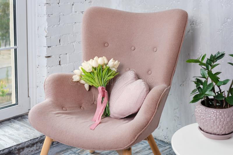 Stylish pink armchair with heart shaped pillow and bouquet of tulips in a bright minimalist interior. Romantic morning at home. stock photos
