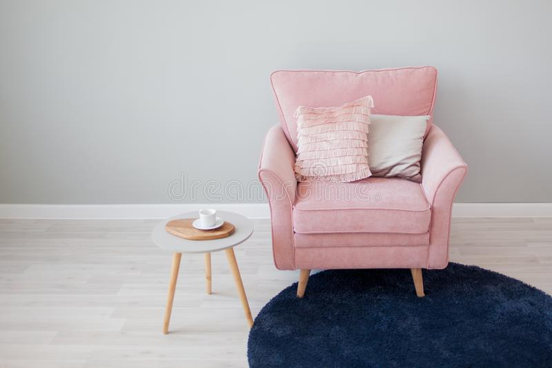 Stylish pink velvet chair with pillows. Stands against a light gray wall. stock image