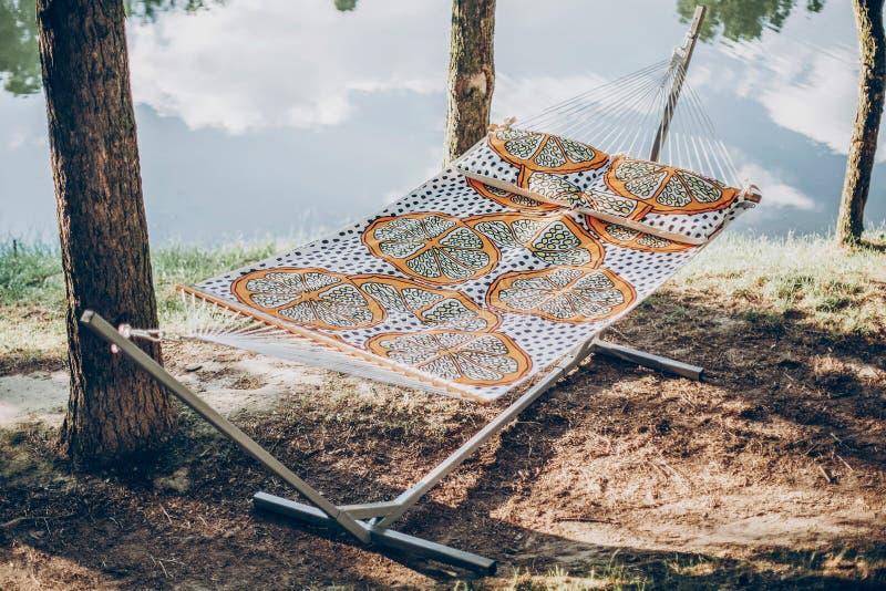 Stylish polka dot hammock near lake at summer vacation camp, boho hammock hanging outdoors, family camping trip concept stock photography