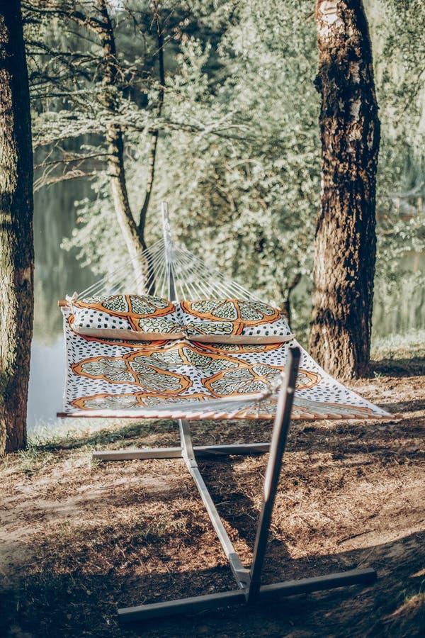 Stylish polka dot hammock near lake at summer vacation camp, boho hammock hanging outdoors, family camping trip concept stock photos