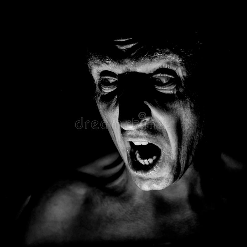Stylish portrait of adult caucasian man with very angry face and who seems like maniac or devil. royalty free stock image