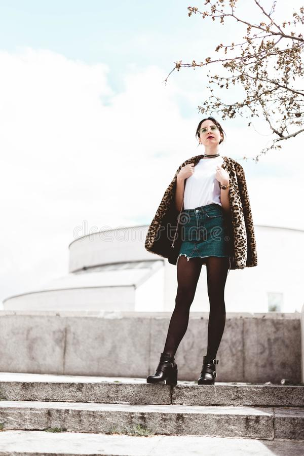 Stylish portrait of young woman wearing trendy animal, leopard print faux fur coat, fashion sunglasses, posing in Madrid city royalty free stock photo