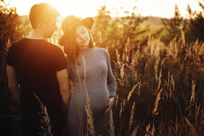 Stylish pregnant couple holding hands on belly and embracing in sunny light in autumn park. Happy young parents, mom and dad, stock photo