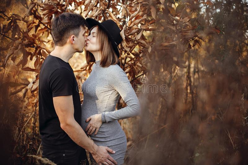 Stylish pregnant couple holding hands on belly in sunny light in autumn park. Happy young parents, mom and dad, hugging baby bump royalty free stock images