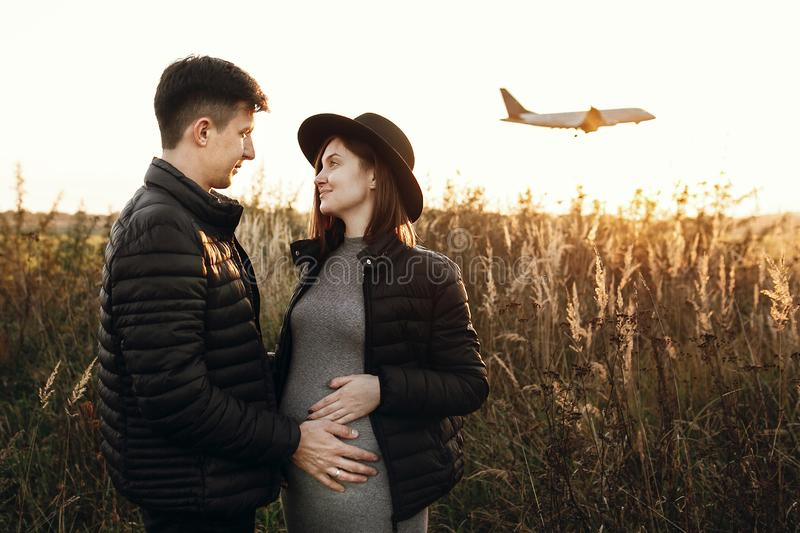 Stylish pregnant couple holding hands on belly in sunny light in autumn park. Happy young parents, mom and dad, hugging baby bump. And smiling, enjoying stock photography