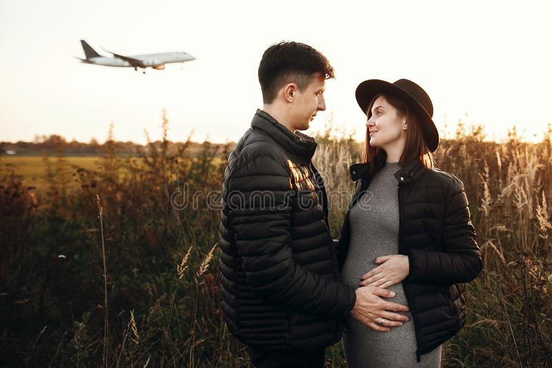 Stylish pregnant couple holding hands on belly in sunny light in autumn park. Happy young parents, mom and dad, hugging baby bump. And smiling, enjoying stock images
