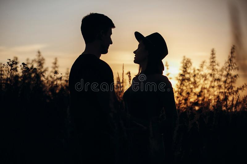 Stylish pregnant couple silhouettes in sunny light in autumn park among grass. Happy young parents, mom and dad, hugging baby bump. Enjoying beautiful moment royalty free stock image