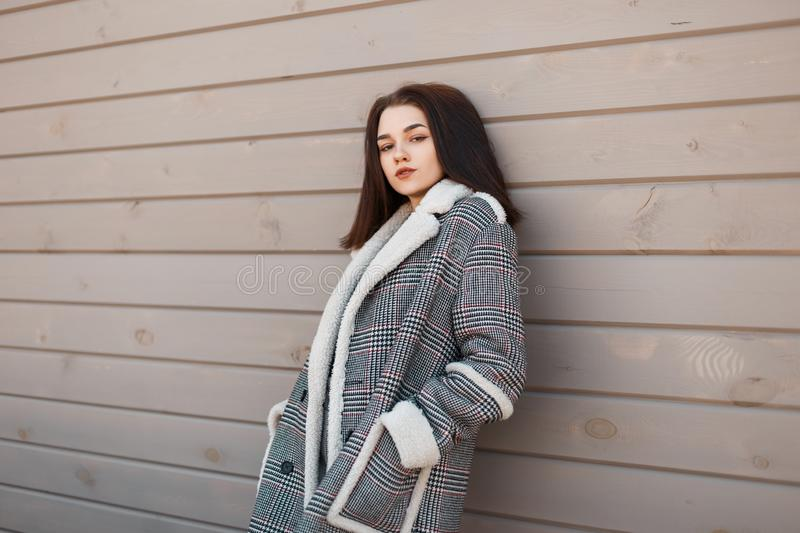 Stylish pretty young woman in a checkered vintage gray jacket with white fur relaxes standing near a beige wooden wall in the city stock photos