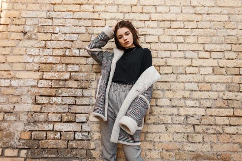 Stylish pretty young woman in vintage gray trousers in a trendy plaid spring jacket in a trendy T-shirt stands. Near a old brick wall in the city. Cute modern royalty free stock image