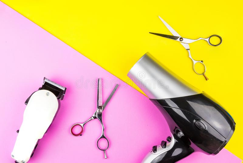 Stylish Professional Barber Scissors, White electric clippers and hair dryer on yellow and pink background. Hairdresser salon stock image
