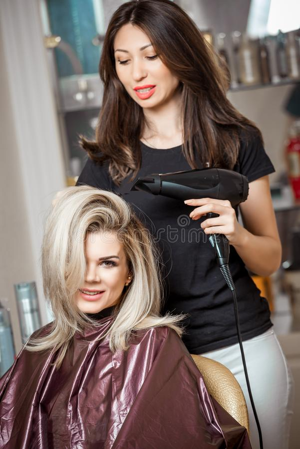 Stylish professional, hairdresser doing hairdoing to the client with a hair dryer on the background of the hairdresser`s royalty free stock photography