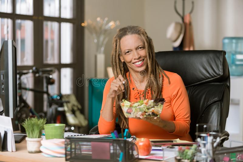 Stylish Woman with Drealocks Eating a Healthy Lunch at her Desk stock photography