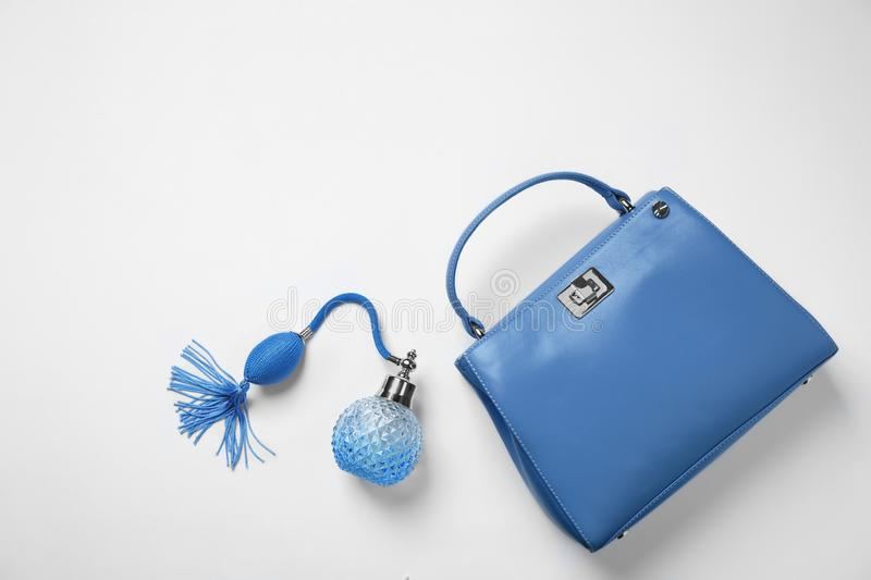 Stylish purse and perfume bottle on background, top view. Classic blue - color of the Year 2020. Stylish purse and perfume bottle on white background, top view stock photography