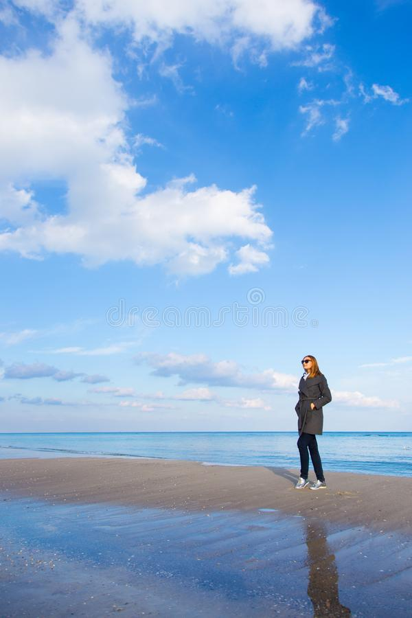 Stylish red-haired girl in dark coat and sunglasses standing on seaside with beautiful sky and water on background stock photos