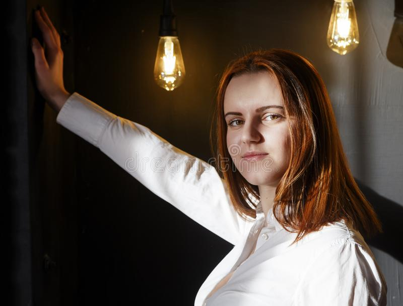 Stylish red-haired girl student look at the camera, hand leaned against the wall, loft interior royalty free stock images